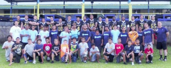 Front row: elementary students. Middle row: Officer Tina (far left), intermediate students and Officer Botelho (far right). Back row: Coach Baldwin (far left) and his Hilo High School football players.