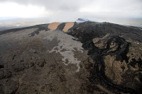 Lava flows from two different vents in Puʻu ʻŌʻō crater have spilled out of the crater and down the flanks of the cone over the past week. This photo shows the new flow, easy to identify with its light gray color, originating from the south spatter cone in Puʻu ʻŌʻō crater (the spatter cone is visible as a bump on the crater floor). This flow was still active the morning of April 28, 2014 and had traveled a short distance southeast. Another flow, originating from the north spatter cone in Puʻu ʻŌʻō crater, is not visible in this photograph. Photo courtesy of USGS/HVO