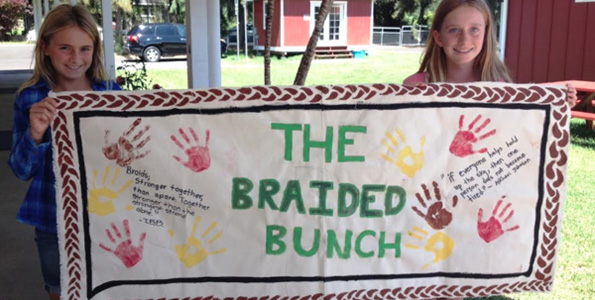 Parker 6th graders hold a sign they made about the significance of the braid, after their recent visit to Pukalani Stables. (Photo courtesy of Parker School)