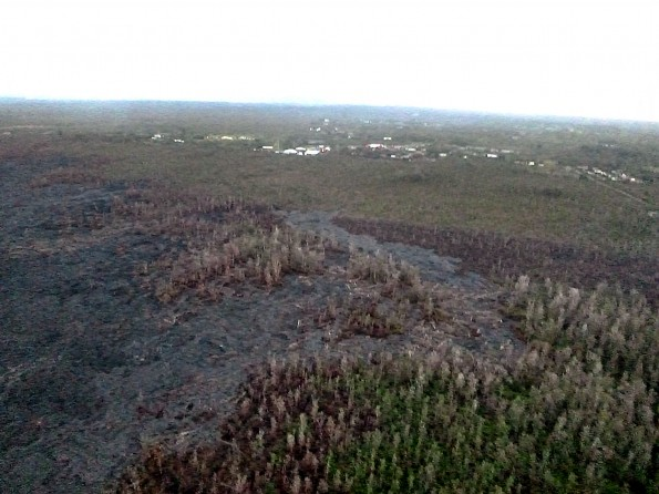 Image from the Friday, March 13, 2015 overflight of the Kilauea June 27th Lava Flow.  The view from the south flow margin, looking down slope towards Hwy 130, Pahoa Marketplace, and Apaa Street. Photo courtesy of Hawaii County Civil Defense