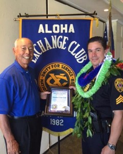 Aloha Exchange Club member Joey Estrella presents an 'Officer of the Month' award to Detective Grant Todd.