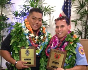 Police Officer Ryan Pagan and Fire Captain Garrett Kim display plaques from the Aloha Exchange Club of East Hawaiʻi.