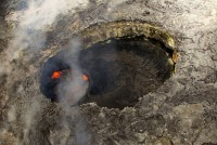 In the western portion of Puʻu ʻŌʻō Crater, there has been a small pit for nearly a year. The pit is about 60 m (200 feet) wide, and a small circular lava pond resides beneath the overhanging west rim of this pit. Photo taken Saturday, March 25, 2016 courtesy of USGS/HVO