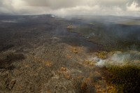 Another view, looking west, showing the activity along the forest boundary and northern flow margin. Scattered breakouts were burning forest in this area. In the upper left portion of the image, Puʻu ʻŌʻō can be seen. Photo taken Saturday, March 25, 2016 courtesy of USGS/HVO