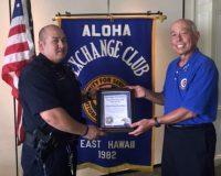 "Aloha Exchange Club member Joey Estrella presents an ""Officer of the Month"" award to Officer Daniel Kuwabara."