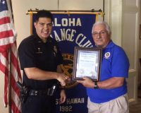"Aloha Exchange Club member John Stewart presents an ""Officer of the Month"" award to Officer Gregory Horton."