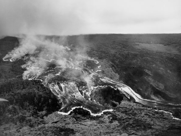 This rapidly moving ʻaʻā lava flow was one of several that advanced down the west flank of Mauna Loa during the volcano's 1950 eruption. The massive flow, tens of meters (yards) high, traveled from the Southwest Rift Zone vent to the ocean, a distance of about 18 km (11 mi), in around 18 hours. Two earlier flows from this eruption reached the ocean in as little as three hours. All three flows crossed Highway 11 as they advanced to the sea. In this black-and-white aerial photo, incandescently hot areas on the flow appear white. Photo credit: Air National Guard, 199th Fighter Squadron.