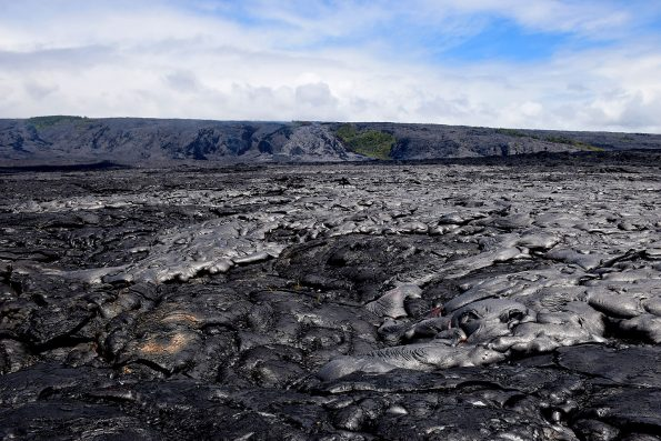 """As Kīlauea Volcano's active pāhoehoe flow spreads across the coastal plain on July 6, the new lava appeared more shiny or silvery compared with the older lava beneath it. Molten """"toes"""" of lava breaking out from the leading edges of the flow can be seen in the lower right quadrant of the photo.  USGS photo."""
