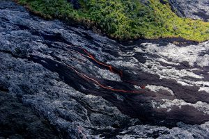 Channelized ʻaʻā lava flows were still active on the steep sections of the pali. Dark brown areas are recently active ʻaʻā, and the shiny gray areas are pāhoehoe lava. Photo taken Friday, July 8, 2016 courtesy of USGS/HVO