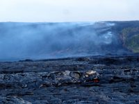 During early morning field observations, a large breakout of lava near the base of Pūlama Pali (steep fault scarp in background) was visible through fumes from the lava tube and heat shimmer from lava on the coastal plain. The approximate location of the lava tube feeding Kīlauea's active lava flow is visible as degassing sources (white fume) on the pali. Photo taken Friday, July 22, 2016 courtesy of USGS/HVOThe flow was about 615m from the road and 760 m from the ocean.