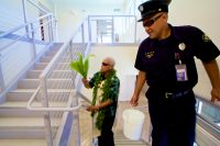 Kahu Isaia Kealoha walks through the new Hilo International Airport Aircraft Rescue and Firefighting Station sprinkling holy water with ti leaf to bless the facility. Photography by Baron Sekiya   Hawaii 24/7