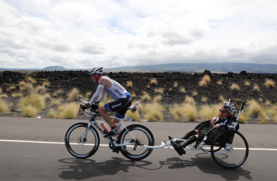 Jeff Agar pulls his son, Johnny, who suffers with cerebral palsy, along the bike course. (Photo courtesy of Ironman)
