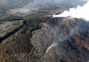 On May 24, 2016, two new flows broke out on the flanks of the Puʻu ʻŌʻō cone on Kīlauea Volcano's East Rift Zone. The silvery sheen of new lava erupting from the northern 61f breakout (center) and eastern 61g breakout (upper left) stands out in contrast to the older flows on and around Puʻu ʻŌʻō (right). The 61f flow stagnated within two weeks, but the 61g flow, which advanced downslope and reached the ocean on July 26, 2016, remains active today. USGS photo.
