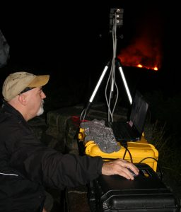 A U.S. Geological Survey scientist used a custom-built, high-speed camera to remotely measure the temperature of spattering lava on the surface of Kīlauea Volcano's summit lava lake (background). This particular experiment, conducted from the Jaggar Museum overlook in Hawaiʻi Volcanoes National Park on December 10, 2016, was part of a NASA-funded research project. USGS photo.