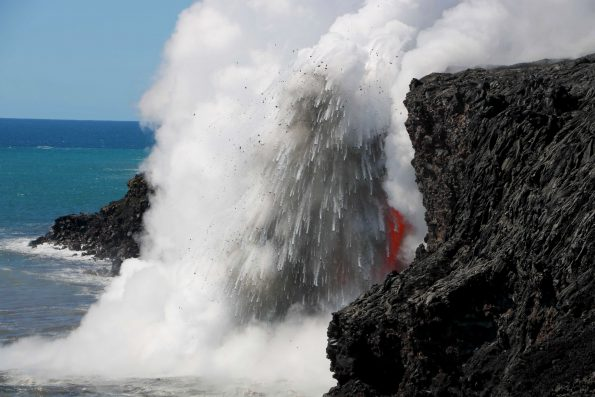 As seen in late January, the interaction of molten lava and cold seawater at the Kamokuna ocean entry produces an explosion, sending hot fragments and steam high into the air. The sea cliff in this image is about 15 meters (50 feet) high. USGS photo.