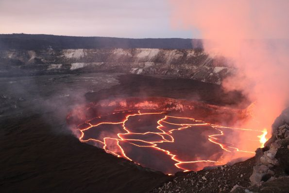 Sunset view of the Kīlauea summit lava lake showing an active area of spattering at the right margin. Jagged openings between cooler crustal plates reveal molten lava. HVO is faintly visible on the Kīlauea Caldera rim at upper left. USGS photo February 13, 2017.