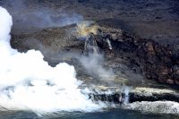 View of the Kamokuna lava delta and the lava structure encasing the lava stream where it emerges from the mouth of the lava tube in the face of the sea cliff. Photo taken Wednesday, May 31, 2017 courtesy of USGS/HVO