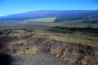 Mauna Loa looms in the background behind the USGS Hawaiian Volcano Observatory and Hawai'i Volcanoes National Park Jaggar Museum complex, perched at the summit of Kīlauea Volcano. The cliff in the foreground is Kīlauea's caldera rim. Photo taken Wednesday, May 31, 2017 courtesy of USGS/HVO