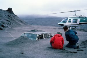 USGS geologist Don Swanson (in red) and his colleague, Jim Moore, view a car filled with ash deposits from the May 18, 1980, eruption of Mount St. Helens.