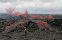 On March 6, 2011, USGS Hawaiian Volcano Observatory scientists were stationed along Kīlauea Volcano's East Rift Zone to monitor the progression of erupting fissures that had opened west of Pu'u 'Ō'ō the day before. Lava spewing from this fissure (background) reached heights up to 30 m (100 ft) and produced a massive lava flow, visible behind the HVO scientist. This event, known as the Kamoamoa fissure eruption, lasted only five days. USGS photo, N. Richter
