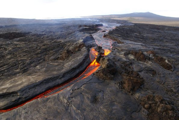This perched lava channel, which was as much as 150 feet (45 meters) above the ground, carried lava downslope from the Pu'u 'Ō'ō Fissure D vent during episode 58 of  Kīlauea Volcano's ongoing East Rift Zone eruption. The channel was the main path for lava between July and November 2007. Episode 58 continued until early March 2011. Pu'u 'Ō'ō is visible at upper right.  USGS photo by J. Kauahikaua, October 7, 2007.