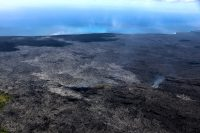 Aerial view from the top of the pali, looking towards the ocean entry. The lighter silver lava flow breakouts over the past week have spread out at the base of the pali. The closest location of activity is 1.6 km (1 mile) from the gravel road. Fume is rising from the main lava tube on the right of the image. The coastal entry plume is on the horizon, staying close to the ground near the Kamokuna delta. Photo taken Thursday, September 21, 2017 courtesy of USGS/HVO