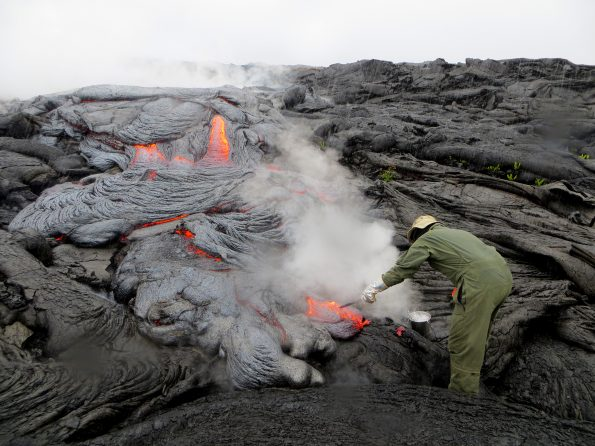 A USGS Hawaiian Volcano Observatory geologist collects a sample of pāhoehoe lava on Kīlauea Volcano's East Rift Zone. Steam rising from the flow resulted from heavy rain falling on the hot lava. Analyses of this and other samples provide information on the changing temperatures of Kīlauea lavas, which, in turn, reveal information about the volcano's internal plumbing and magma transport processes. USGS photo by J. Babb
