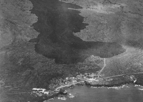 The dark-colored 'a'ā flow advancing toward the South Kona coastal village of Ho'ōpūloa (foreground) on April 17, 1926, is a reminder of why Island of Hawaiʻi residents should be aware of the hazards posed by the volcanoes on which they live. This flow was fed by eruptive vents that opened high on Mauna Loa's Southwest Rift Zone three days earlier. It was 1,500 feet wide and about 30 feet high in this aerial photo, but the 'a'ā flow continued to widen and thicken as it pushed through the village and reached the ocean on the morning of April 18. Photo courtesy of Army Air Corps, 11th Photo Section.