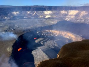 "On January 8, 2018, Kīlauea Volcano's summit lava lake level was 38 m (125 ft) below the rim of ""Overlook crater,"" the small crater that formed above the active vent in Halemaʻumaʻu. The lava lake continuously emits elevated levels of sulfur dioxide gas and erupts small, but measurable, amounts of Pele's hair and other ash-sized tephra (airborne lava fragments) that accumulate on the rim of Halemaʻumaʻu (lower right) and areas downwind of the lake. USGS photo by J. Sutton."