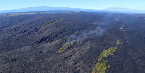 Spectacular aerial view of Kīlauea Volcano's East Rift Zone lava flows advancing over Pūlama pali in mid-December 2017. As surface lava flows moved through the center kipuka (forested area) on the pali, smoke rose from the burning vegetation. Gases emitted from Pu'u 'Ō'ō, the source of the 61g lava flow, can be seen in the distance above the smoke from the burning kipuka. Mauna Loa (left) and Mauna Kea (right) are visible in the far distance. If you look carefully in front of Mauna Loa, you can see the gas plume rising above Halemaʻumaʻu at the summit of Kīlauea. Capturing both the summit and East Rift Zone eruptions in one photo is a rare sight! USGS photo by C. Parcheta.