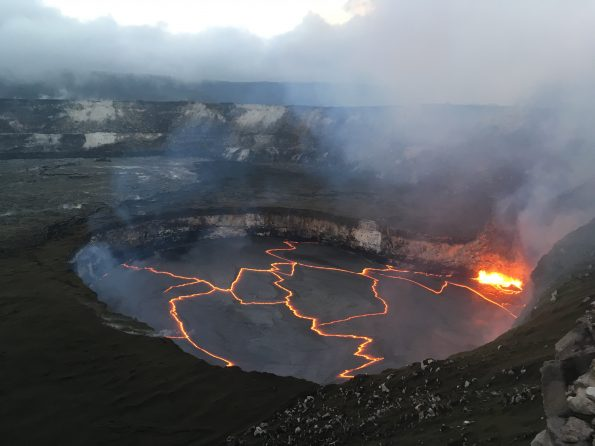 Early evening view of the lava lake within Halemaʻumaʻu crater at the summit of Kīlauea Volcano on January 30, 2018, when the lake level was 27 m (88 ft) below the crater floor. The bright yellow area of spattering marks the location where the circulating lava descends into the lake, thereby releasing gases trapped beneath the solid black crust on the lake surface. The area around Halemaʻumaʻu remains closed due to ongoing volcanic hazards associated with the lava lake, including high levels of sulfur dioxide gas and unexpected rockfalls and explosions. USGS photo by M. Patrick.