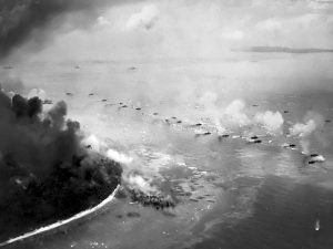 The first wave of LVT(A)s move toward the invasion beaches, passing through the inshore bombardment line of LCI gunboats, 15 September 1944. Cruisers and battleships are bombarding from the distance. The landing area is hidden bu dust and smoke. Photographed from a USS Honolulu (CL-48) plane. Source: NARA 80-G-283533.