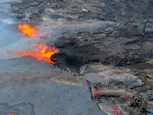 The summit lava lake level remained high throughout Wednesday, April 25, sending occasional overflows across the floor of Halema'uma'u. A spattering site (upper left) poured lava into a small overflow directed to the north. A passive overflow of the lava lake rim (bottom right) sent a more sluggish lava flow onto the floor of Halema'uma'u. Just left of center in this photo, a spattering source has constructed a spatter rampart on the lake margin. Photo taken Wednesday, April 25, 2018 courtesy of U.S. Geological Survey