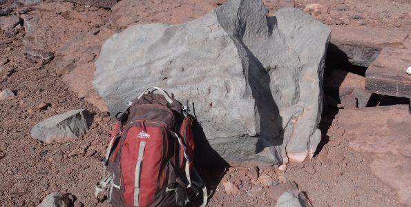 This light gray block of rock (backpack for scale) is part of the approximately 830-year-old explosion deposit on the northwest rim of Moku'āweoweo, the summit caldera of Mauna Loa. USGS photo by F.A. Trusdell.