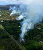 An intrusion of magma into Kīlauea Volcano's lower East Rift Zone resulted in an eruption in Leilani Estates in the lower Puna District on the Island of Hawaiʻi. The first four fissures to erupt in the subdivision are shown here on May 4, emitting copious amounts of hazardous sulfur dioxide gas. Pu'u 'Ō'ō (top center), which is about 20 km (12.4 mi) uprift of Leilani Estates, can be seen on the far horizon (top center). As of May 6, at least 10 fissures have erupted in the subdivision. USGS photo by T. Neal.