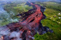 Helicopter overflight of Kīlauea Volcano's lower East Rift zone on May 19, 2018, around 8:18 AM, HST. 'A'ā lava flows emerging from the elongated fissure 16-20 form channels. The flow direction in this picture is from upper center to the lower left. Photo taken Saturday, May 19, 2018 courtesy of U.S. Geological Survey