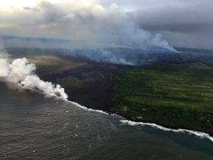 The fissure complex, pictured in the upper right, continues to feed a meandering lava flow (in the center). Lava in the easternmost lobe is entering the ocean (white plume). Photo taken Tuesday, May 22, 2018 courtesy of U.S. Geological Survey