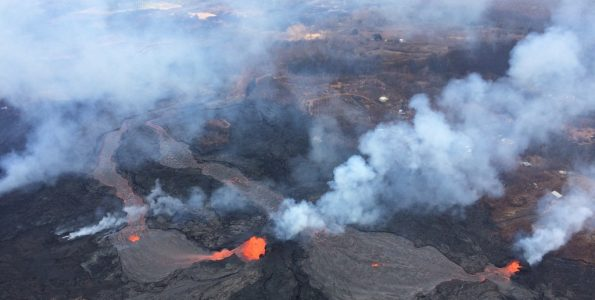 Fissures 6 (left) and 13 (right), with lava flows merging into one channel that flows into the ocean at the western-most entry. Note plume in distance at the ocean entries (top left). Photo is from an overflight at mid day. Photo taken Friday, May 25, 2018 courtesy of U.S. Geological Survey