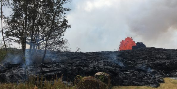 """When molten lava encroaches on grassland, forests, or other vegetated land, subsurface pockets of natural gas from the burning plant material can ignite, causing a blast known as a """"methane explosion."""" To avoid this hazard, keep a safe distance—at least tens of yards—from the margin of an active lava flow in vegetated areas. USGS photo."""