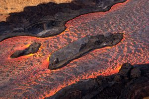 Lava flows around islands in the lava channel. The direction of flow is from the upper right to lower left. Field crews can make a rough calculation of velocity by timing large blocks as they pass between two landmarks that are a known distance apart. Photo taken Saturday, June 30, 2018 courtesy of U.S. Geological Survey