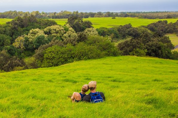 A couple enjoying the view from Pu'u o Lokuana cindercone in the Kahuku Unit. NPS Photo/Janice Wei ​