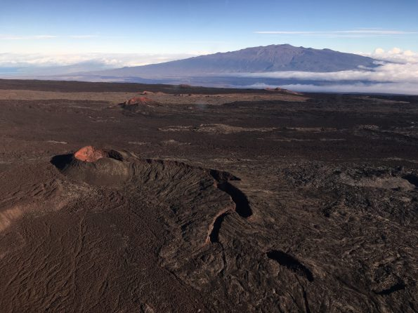 View of cinder cones in the Northeast Rift Zone near the summit of Mauna Loa. View to the north-northeast with Mauna Kea in the background. Mauna Loa has erupted 33 times since 1843, most recently erupting in 1975 and 1984. Photo credit: Matt Patrick, USGS
