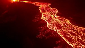 USGS Mavic Pro drone image of the fissure 8 lava channel looking toward the vent. Overflows can be seen as incandescent spots beyond the channel margins. Drone flights and resultant imagery help scientists better identify areas of channel overflows and active flow advancement. Incandescence (glowing) lava is easier to identify in the dark versus during daylight hours. Photo taken Monday, July 2, 2018 courtesy of U.S. Geological Survey