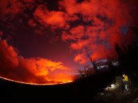 Fisheye lens photograph of a USGS geologist making observations of the fissure 8 lava channel at sunset July 3, 2018. The field crew is at a high point overlooking the channel near where it makes a 90 degree turn around Kapoho Crater and flows south. The glow of the fissure 8 vent is the bright spot in the center of a different cone, Halekamahina. Photo taken Wednesday, July 4, 2018 courtesy of U.S. Geological Survey