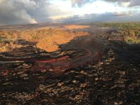 """The lava channel from fissure 8 jumped its banks near Kapoho Crater where the channel makes a 90 degree bend. The flow within the channel was diverted around a constricted area and joined the channel again """"downstream"""" to the south (left). Photo taken Wednesday, July 4, 2018 courtesy of U.S. Geological Survey"""