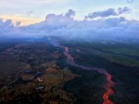 """An early morning aerial view (looking west) of the fissure 8 lava channel. Downstream of the vent, the channel splits to form a """"braided"""" section in the lava channel, and, this morning, the north (right) arm of the braided section appeared to be partially abandoned. Lava was still visible in part of the northern braid, but the lower section was only weakly incandescent. During today's overflight, lava within the channel generally appeared to be at a lower level than in previous days. Photo taken Thursday, August 2, 2018 courtesy of U.S. Geological Survey"""