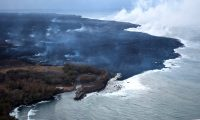 During this morning's overflight, the ocean entry laze plume was being blown offshore, allowing this fairly clear view (looking northeast) of the Pohoiki boat ramp at Isaac Hale Beach Park. Incandescent (glowing red) spots of lava can be seen within the flow field beyond the boat ramp. HVO geologists also observed a few oozes of lava on or near the western flow margin, but all appeared weak as of 6:00 a.m. HST. Photo taken Thursday, August 2, 2018 courtesy of U.S. Geological Survey