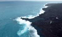 """On July 13, we posted an image of a tiny """"island"""" forming just offshore of the Kapoho ocean entry. Today, that feature—likely a submarine tumulus of lava that built up underwater and emerged above sea level—is no longer an """"island."""" It now looks more like a peninsula, attached to the coast by a black sand tombolo, a sandy isthmus, creating a feature known as a """"tied island."""" Whether or not it will withstand wave erosion over time remains to be seen. Photo taken Thursday, August 2, 2018 courtesy of U.S. Geological Survey"""