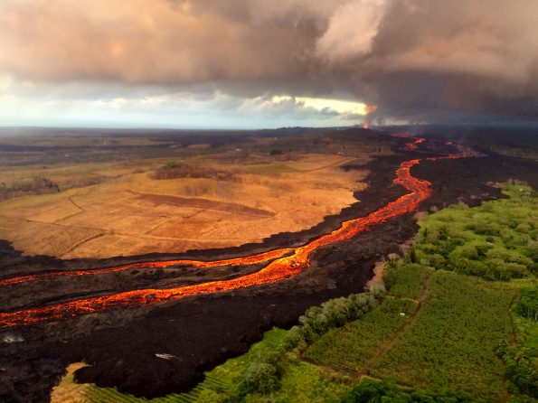The fissure 8 vent (far distance, upper right) continues to feed an active lava channel on Kīlauea Volcano's lower East Rift Zone, shown here on July 26, 2018. Based on several monitoring techniques, the USGS recently estimated that lava is erupting from fissure 8 at a rate of 50 to 150 cubic meters per second (65–196 cubic yards per second), or roughly, 1.1 to 3.4 billion gallons per day. USGS photo by L. DeSmither.
