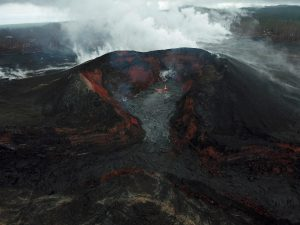 Early this morning, the Unmanned Aircraft Systems team was able to conduct a brief overflight of fissure 8 between passing rain showers, which resulted in abundant steaming on the flow field. This UAS image shows a small pond of lava on the floor of the crater within the fissure 8 cone, with some minor, low-level spattering and slow-moving lava just barely entering (but not heading down) the spillway. Nothing unusual was observed anywhere else on the lower East Rift Zone. Photo taken Monday, September 3, 2018 courtesy of U.S. Geological Survey